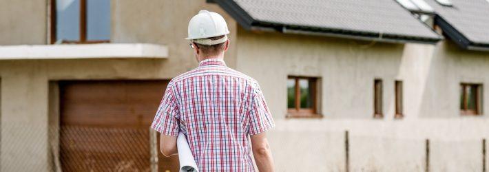 Ein Mann mit Bauhelm auf dem Kopf und Plänen unter dem Arm läuft auf ein Haus zu