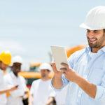 Mehrere Männer mit Bauhelmen und in weißen Hemden sind zu sehen, im Vordergrund arbeitet einer an einem Tablet