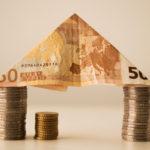 Aus Münzen und einem Geldschein wurde ein Haus gebaut