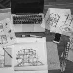 Auf einem Tisch verteilt um einen Laptop liegen viele Pläne, Skizzen und Notizblätter mit Hausfronten und Grundrissen