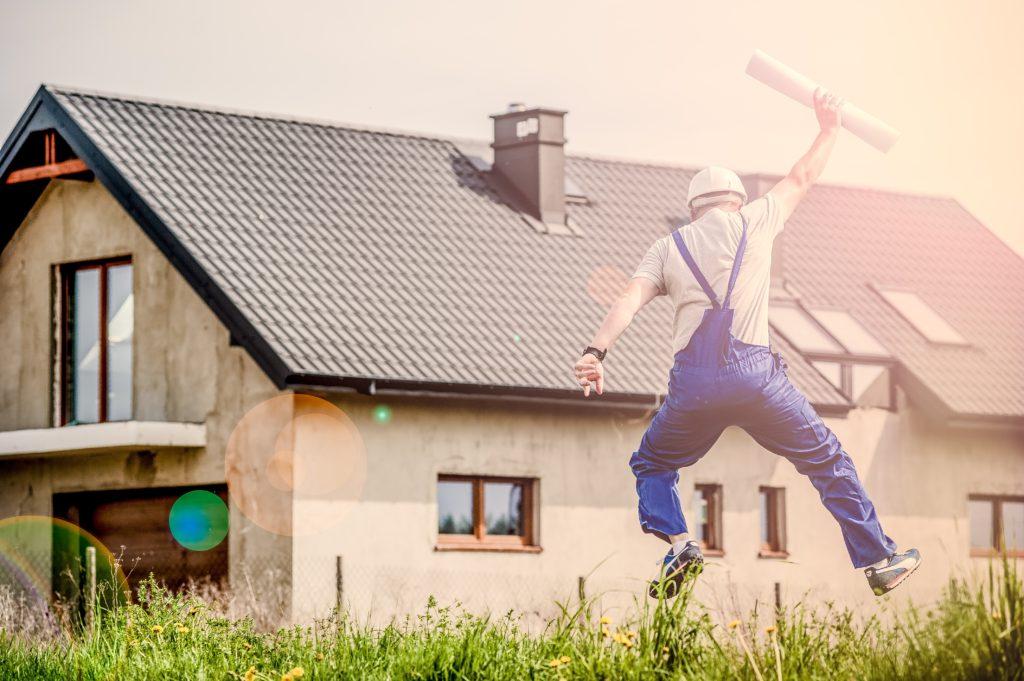 Mann freut sich über fertiges Haus