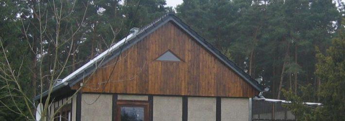 Ein Haus in Holzständerbauweise erbaut steht auf einer grünen wiese