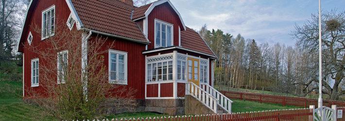 Ein rot-weißes Schwedenhaus mit einem roten Gartenzaun davor