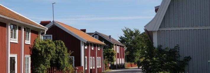 Eine Straße biegt um die Kurve, auf ihr reihen sich viele traditionelle Schwedenhäuser aneinander