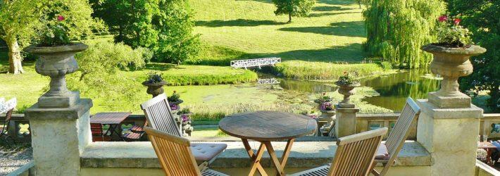 Auf einer mit grauen Steinplatten ausgelegten Terrasse mit blick auf einen grünen Park stehen Gartentisch und Stühle