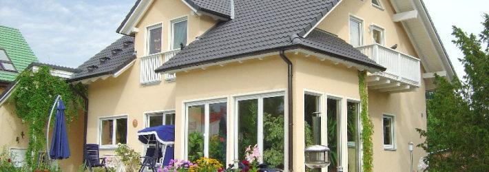 Ein Fertigteilhaus in hellgelb mit weißen Fensterumrandungen und einem grauen Dach