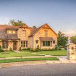 ein Haus in Massivbauweise, gebaut aus hellbraunen Backsteinen mit Garten davor