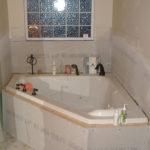 Eine Badsanierung im bewohnten Zustand: Eine Eckbadewanne, noch nicht komplett eingefliest, nur mit Gipskartonplatten verkleidet, auf deren Rand verschiedene Dusch- und Badeartikel stehen.