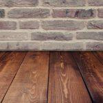 Ein dunkler Holzdielenboden vor einer grauen Backsteinwand