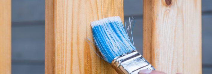 Jemand streicht mit einem breiten Pinsel ein Holzgeländer