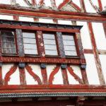Vor dem Restaurieren: Ein altes Fachwerkhaus mit roten Balken, von denen die Farbe abblättert, und weißen Putzflächen.