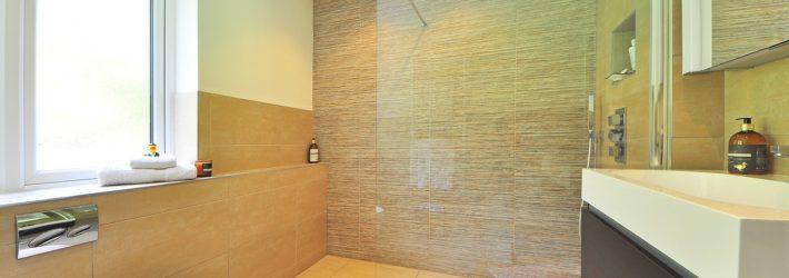 In einem Badezimmer wurden große Bodenfliesen in Beige verlegt