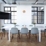 Ein großer Raum mit Esstisch und Stühlen in der Mitte, der Fußboden ist mit Parkett im Fischgräten Verlegemuster gestaltet