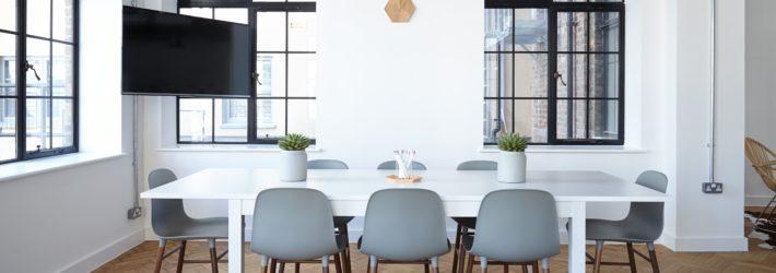 Ein Großer Raum Mit Esstisch Und Stühlen In Der Mitte, Der Fußboden Ist Mit  Parkett