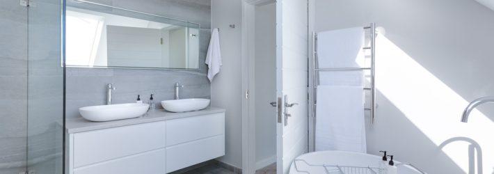 Blick in ein Badezimmer, in dem großformatige Fliesen verlegt wurden. Rechts steht die Wanne, links sind Dusche und Doppelwaschtisch.