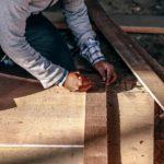 Beim Bau einer Unterkonstruktion für die Terrasse zeichnet ein Mann etwas auf einem Holzbalken an