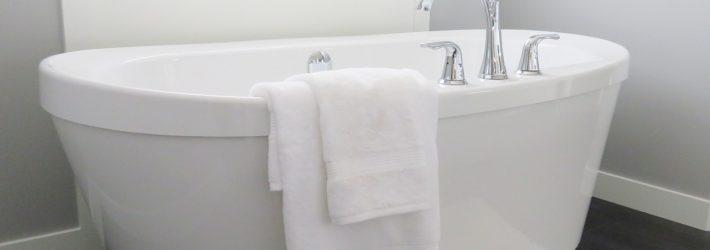 In einem fugenloses Bad steht vor einem Fenster eine weiße, freistehende Badewanne.