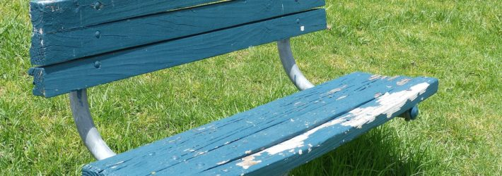 Auf einer grünen Wiese steht eine Holzbank, von der die blaue Farbe langsam abblättert.
