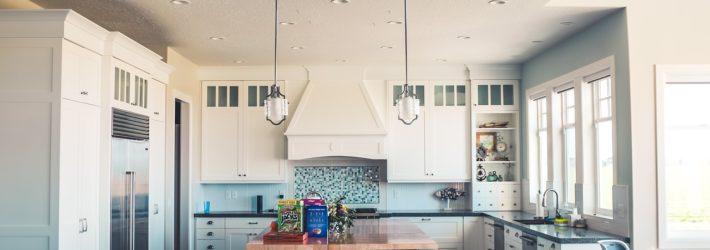 Blick auf eine Küche, in der das Arbeitsdreieck umgesetzt wurde: Links steht der Kühlschrank, rechts ist die Spüle, in der Mitte steht eine Kochinsel.