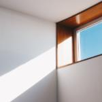 Eine Ecke im Inneren eines Hauses ist zu sehen. Die Wände sind weiß und glatt, oben ist ein Teil eines waagerechten, rechteckigen Fensters zu sehen, durch das die Sonne hereinscheint.