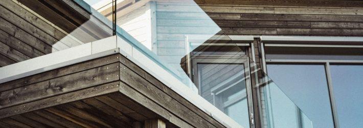Ein Ausschnitt einer Hausansicht, die mit Holz verkleidet wurde. Es sieht bereits ein wenig verwittert aus.