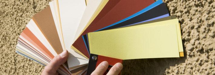 Vor eine Blähton Wand wird ein Farbfächer gehalten.