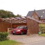 Ein Haus in einer Wohngegend, an dessen Seite ein Carport aus Holz mit durchsichtigem Dach gebaut wurde. Darin steht ein rotes Auto.