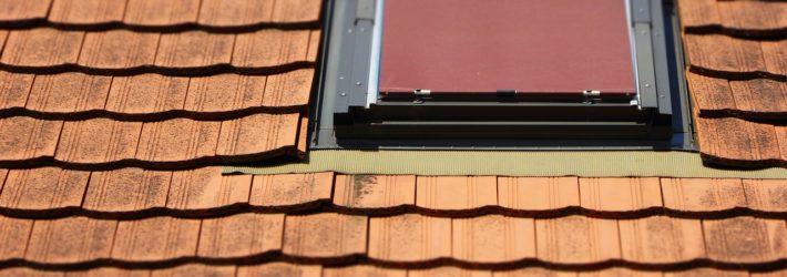 Ausschnitt eines mit roten Ziegeln gedeckten Daches, in das ein Dachliegefenster eingebaut wurde.