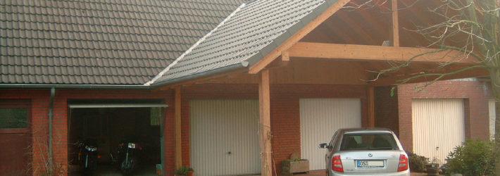 Ein Haus mit mehreren Garagen, vor denen noch ein großer Carport steht.