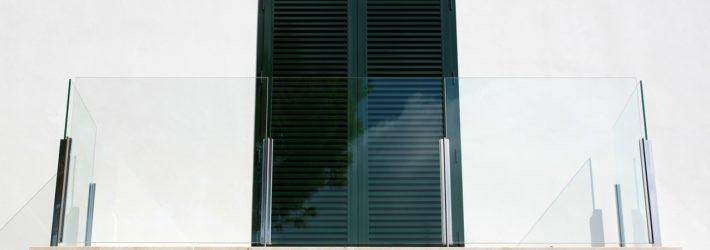 Ein nahezu unsichtbares Balkongeländer aus Glas vor einer weißen Hauswand.