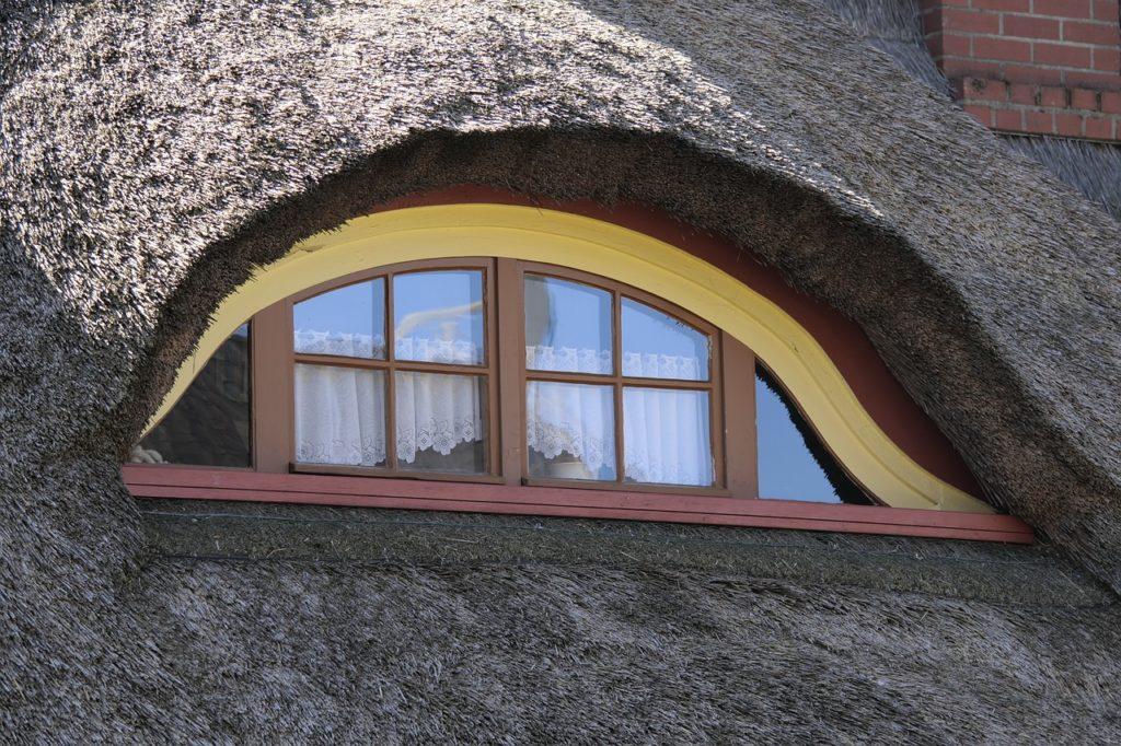 Eine runde Dachgaube, welche mit Reet gedeckt ist.