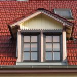 Eine Dachgaube aus hellem Holz und mit zwei Fenstern ragt mittig aus einem mit roten Dachziegeln gedecktem Dach heraus.