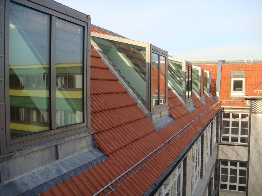Moderne, rechteckige Dachgauben aus Glas stehen auf einem mit roten Ziegeln gedecktem Dach.