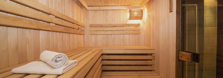 Eine große Sauna von innen. Sie ist mit hellem Holz vertäfelt und hat Bänke aus Holz. Rechts ist der Eingang, links liegen weiße Handtücher auf den Bänken.