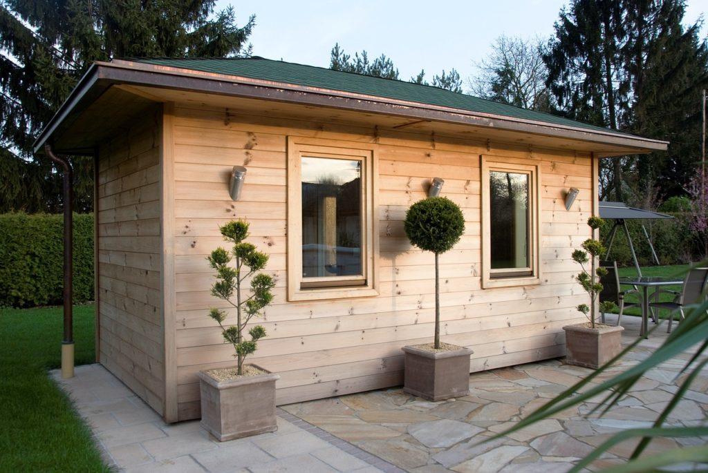 Eine Außensauna aus Holz. Das kleine Häuschen aus hellem Holz steht auf einem Untergrund aus schönen Steinplatten in einem Garten.