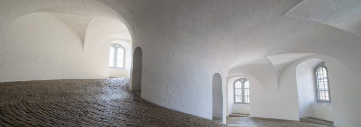 Ein Gang, der um eine Kurve und dabei leicht ansteigend verläuft ist am Boden mit kleinen Pflastersteinen ausgestattet. Die Wände sind mit Kalkfarbe weiß gestrichen.