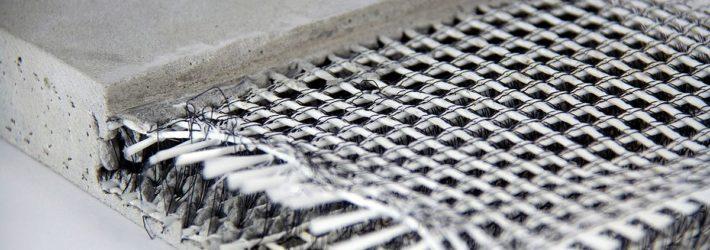 Man sieht auf einem neutralen, hellen Untergrund ein Stück Textilbeton und seinen Aufbau aus Beton und Gewebeschichten.