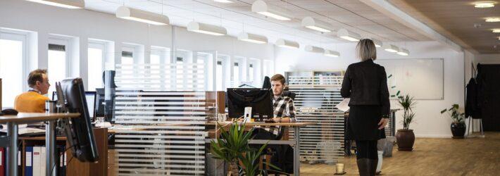 Man sieht einen großen Büroraum, der mit mehreren Schreibtischen gefüllt ist, an dem Menschen arbeiten. Eine Person läuft durch den Gang.