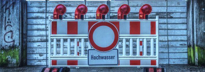 """Vor einer Schutzwand im Freien steht eine Absperrung mit dem Hinweisschild """"Hochwasser""""."""