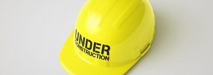 """Ein gelber Bauhelm liegt auf einem weißen Untergrund. Auf ihm steht """"Under Construction""""."""