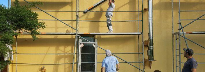 An einem Haus wird von mehreren Männern ein Gerüst aufgebaut.