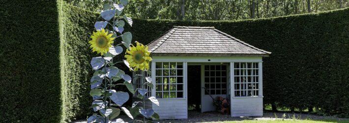 Auf einem grünen Rasen steht in der Ecke, umgeben von einer hohen Hecke ein Gartenhaus. Daneben befindet sich eine Gartenskulptur in Form von Sonnenblumen.