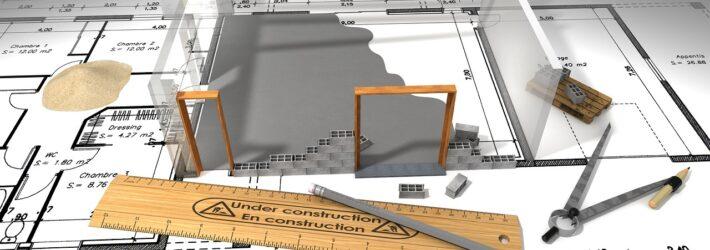 Man sieht einen Bauplan, auf dem Lineal, Zirkel und Stift liegen. Außerdem baut sich gerade ein Bauwerk auf.