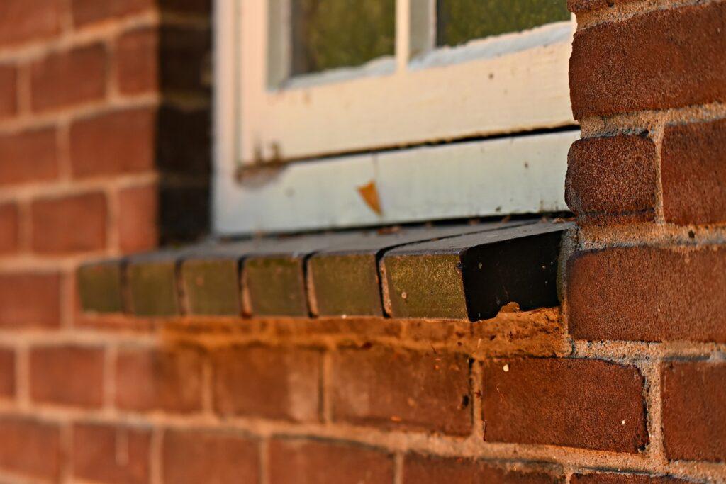 Eine Außenwand eines Hauses ist aus Klinkersteinen gebaut. Das Fensterbrett außen besteht auch aus etwas geneigten Steinen. Darüber das Fenster ist weiß.