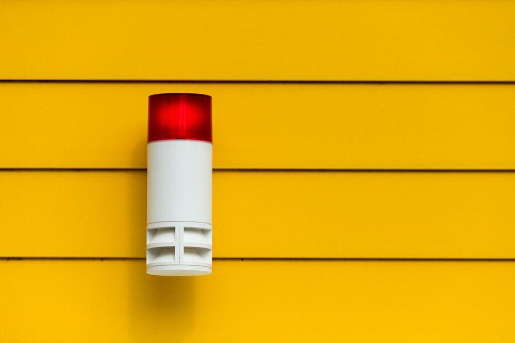 An einer gelben Hauswand ist eine Alarmanlage angebracht mit roter Signalleuchte.