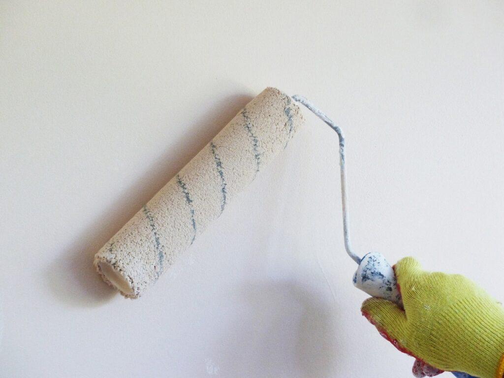 Weiße Farbe wird mit einer Rolle auf eine Wand aufgetragen