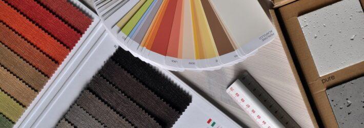 Auf einem Tisch liegen einige Materialien, mit denen zum Beispiel ein Innenarchitekt arbeiten würde: Farbkarten, Stoffproben, Bodenbeläge.