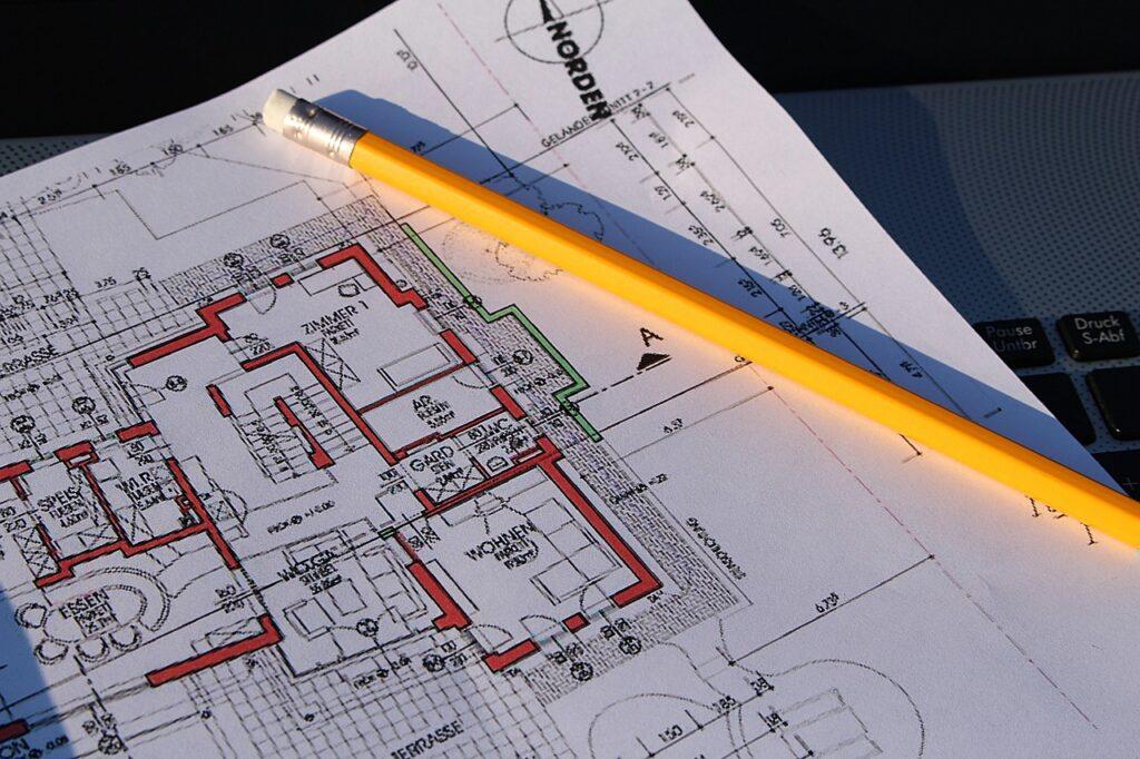 Ein Bauplan ist zu sehen, auf dem ein gelber Bleistift liegt.