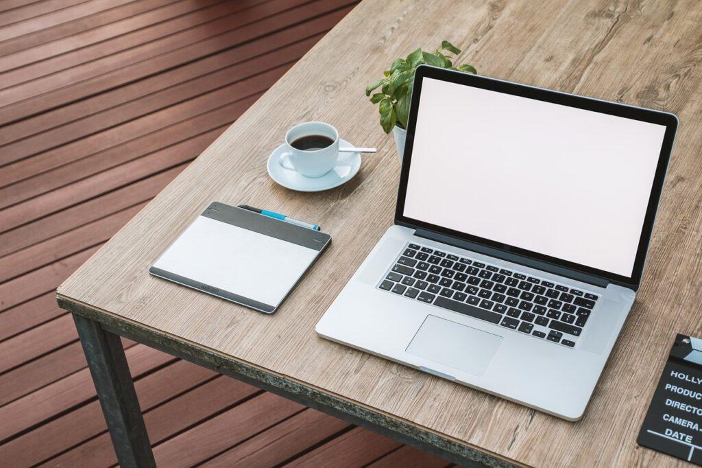 Auf einem Holztisch stehen ein Laptop, eine Kaffeetasse, ein Grafiktablet und eine kleine grüne Pflanze