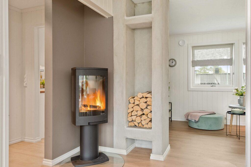 In einem hellen, modernen Wohnraum steht ein Kaminofen, in dem ein Feuer brennt.
